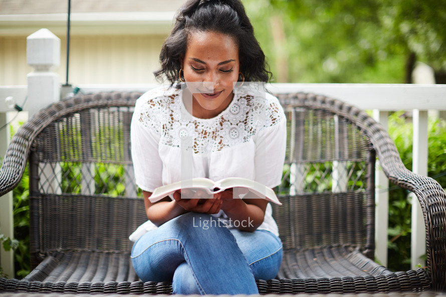 a woman reading a Bible on a porch