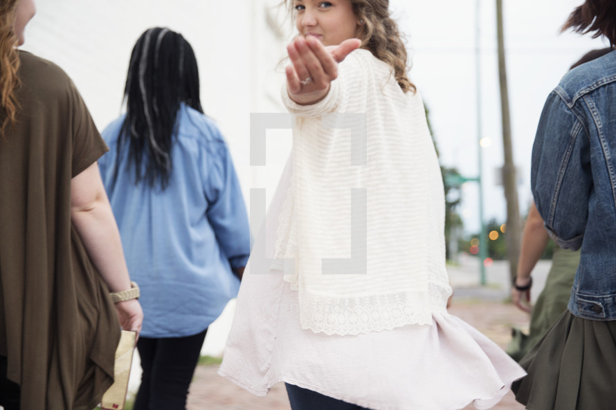 young woman gesturing to follow her