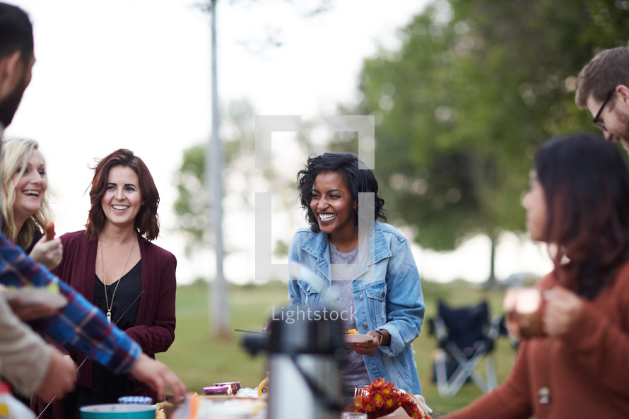 friends gathered around a table at an outdoor picnic party