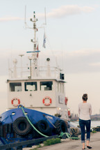 woman walking along a harbor and a tug boat