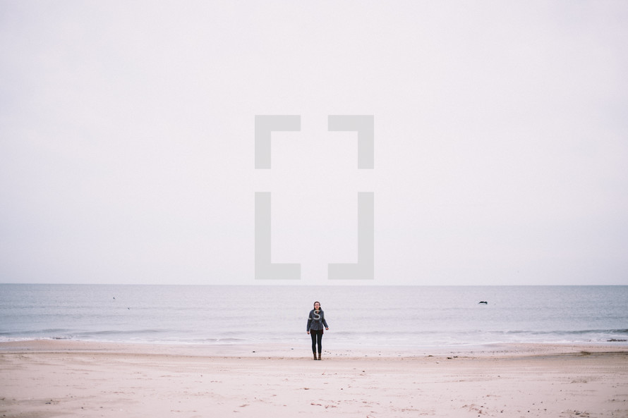 A young woman standing at the edge of the ocean on a beach.
