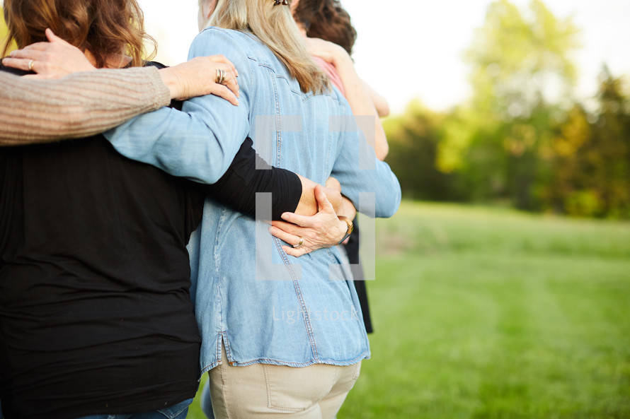 women standing in a backyard praying together outdoors