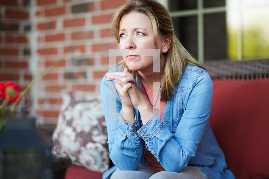 a woman praying sitting on a porch