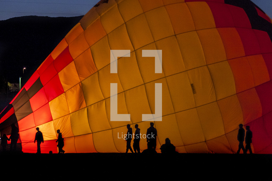 silhouettes in front of a hot air balloon on the ground