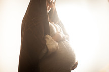 pregnant Mary holding her belly standing in glowing light