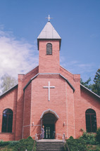 brick church and a woman standing in the doorway
