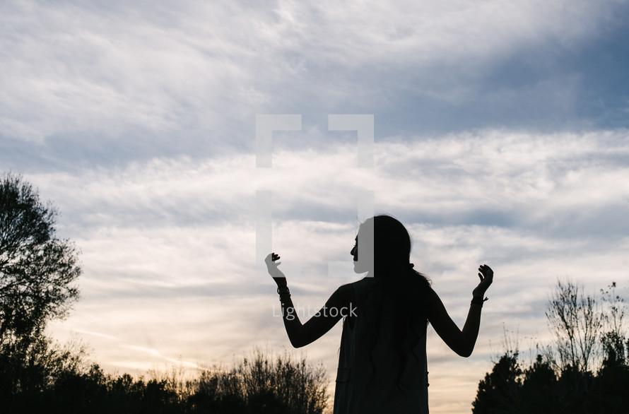 silhouette of a woman with raised hands