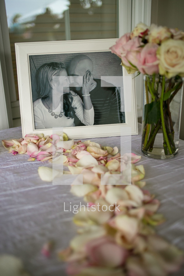 framed picture of a couple and rose petals