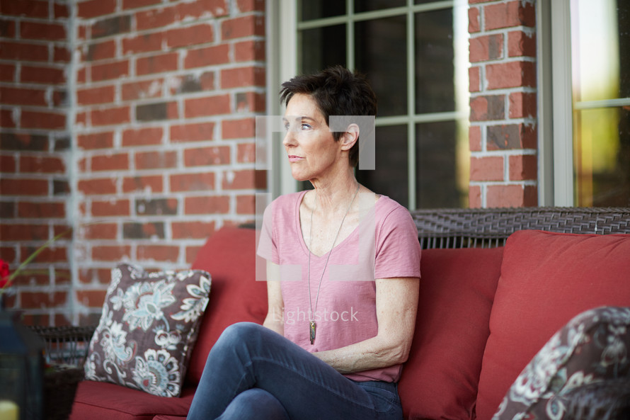 a woman sitting on a porch staring off into space