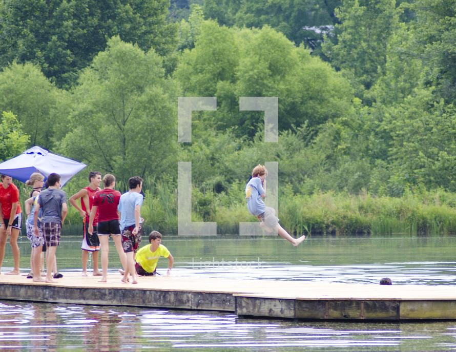 boys at summer camp jumping into lake water