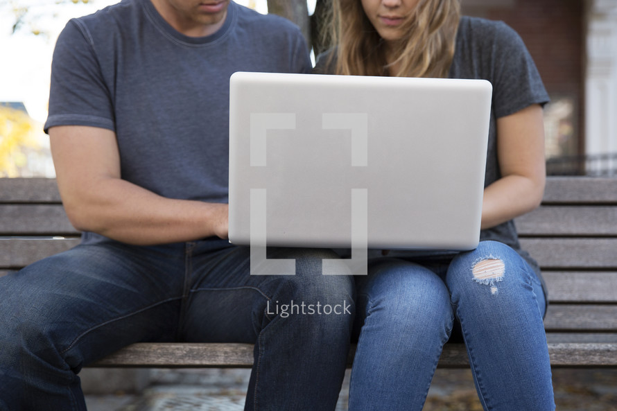 a couple sitting on a bench looking at a laptop computer screen