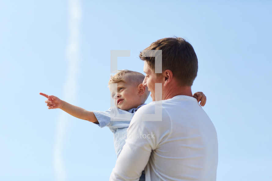 a father holding his son outdoors
