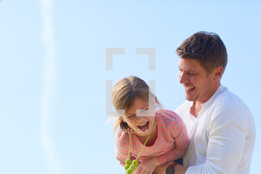 a father holding his daughter outdoors