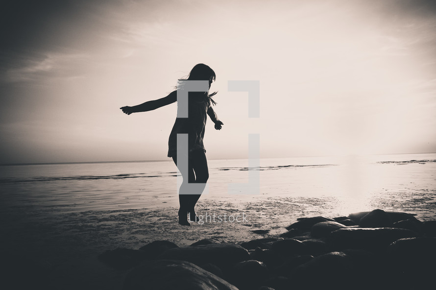 silhouette of a girl jumping on rocks by the ocean
