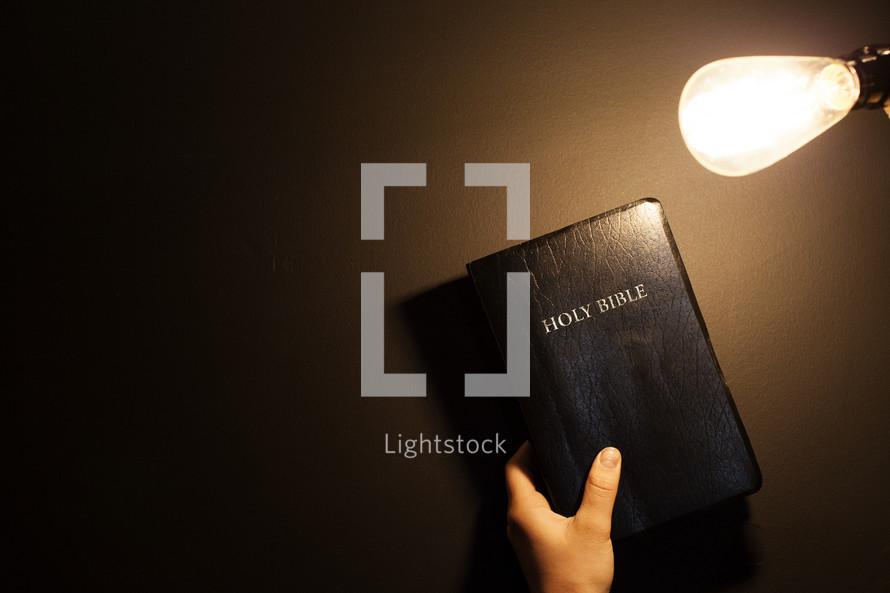 Shining an Edison light on a Bible.
