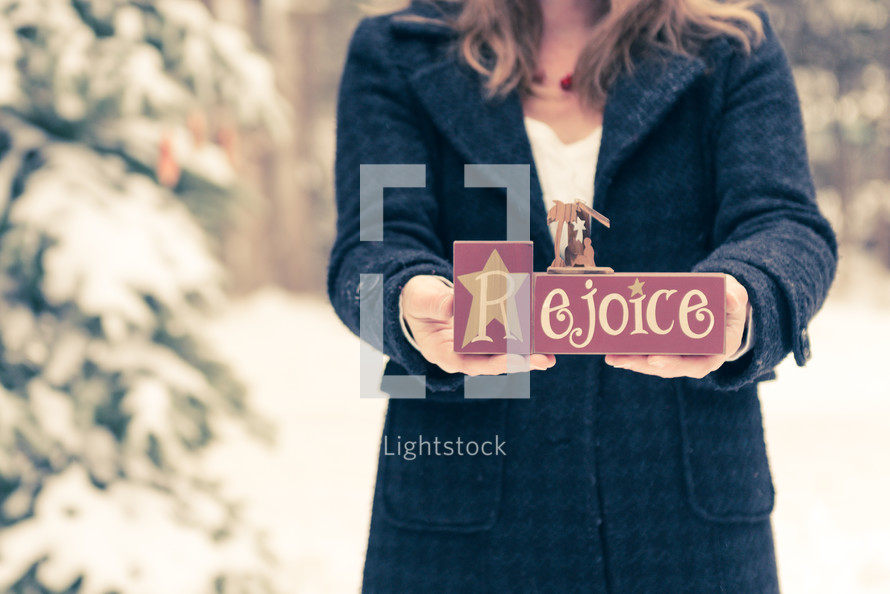 woman holding a rejoice sign