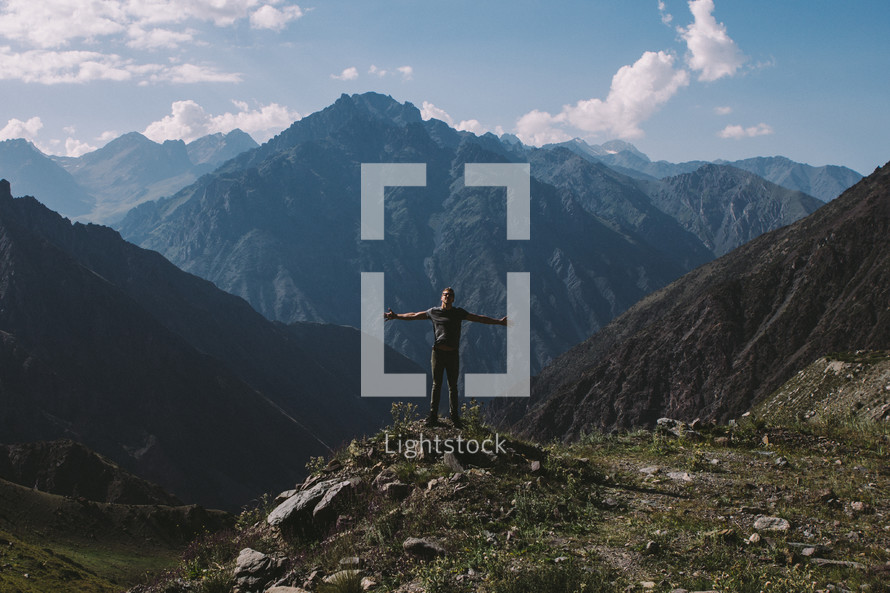 a man with outstretched arms and mountain peaks