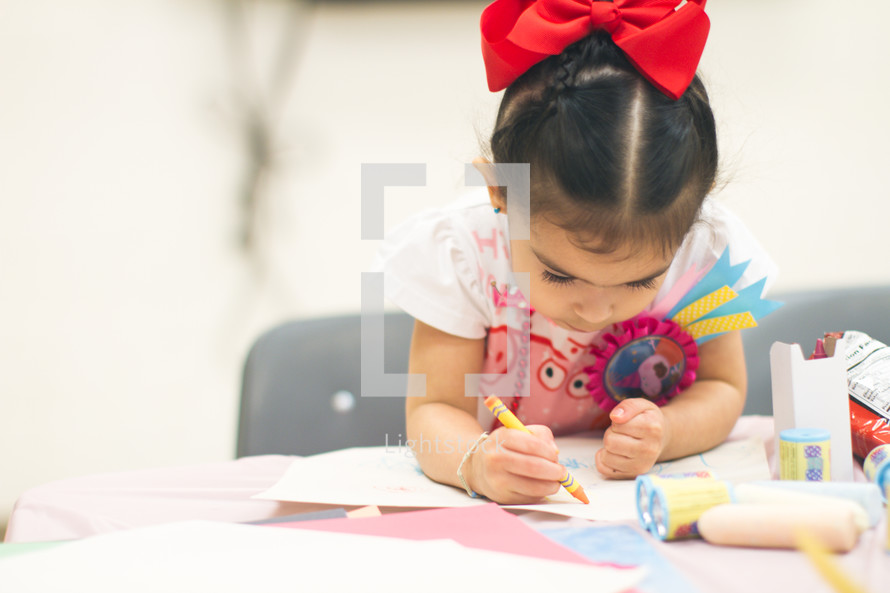 A toddler girl coloring