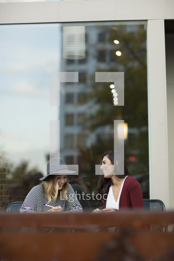 Two women taking and studying together.