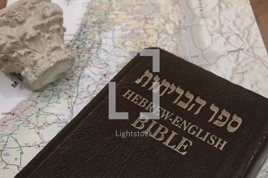 The Bible in Hebrew and English on top of a map of Israel.