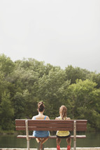 two women sitting on a park bench talking