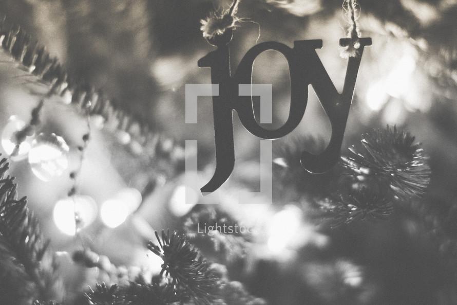 A joy ornament on the Christmas tree