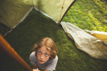A child setting up a tent.