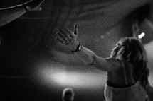 A woman with arms outstretched during a church service.