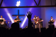 Silhouette of raised hand in the audience of a Christian concert.