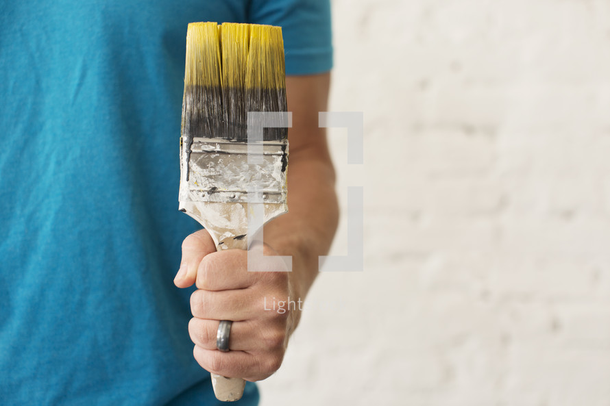 A married man holding a paint brush with yellow paint.