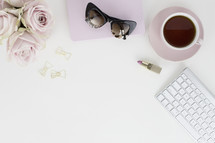 roses, notebook, sunglasses, lipstick, coffee mug, clips, and computer keyboard