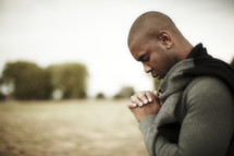 An African American man praying with hands laced
