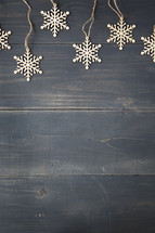 border of snowflake ornaments on a wooden background.