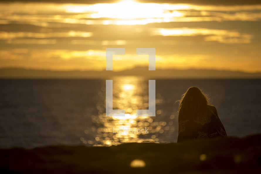 woman sitting on a beach at sunset