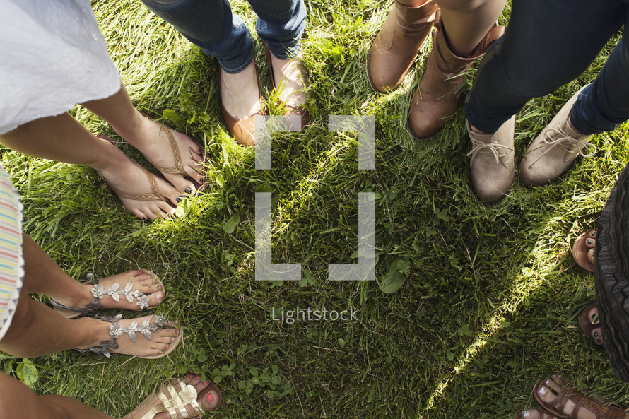 Circle of women's feet standing in the grass.