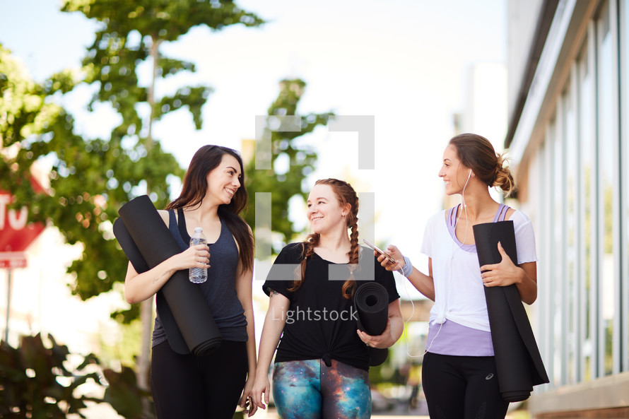 friends walking carrying yoga mats