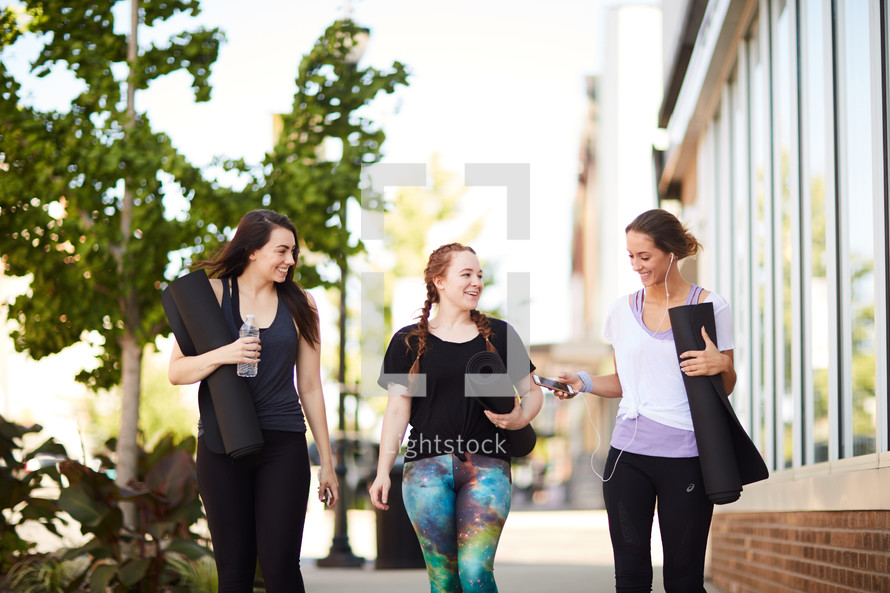 woman carrying yoga mats and listening to iPhone music