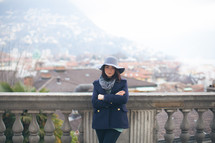a woman in a peacoat and hat with view of a European town n the background
