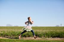 a girl running through a field