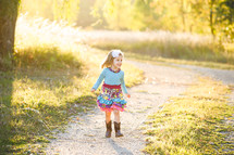 a little girl in a dress and cowboy boots outdoors