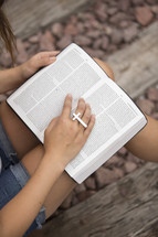 woman reading a Bible and a cross ring