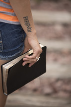 woman with a forgiven tattoo holding a Bible