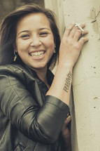 smiling woman with a forgiven tattoo