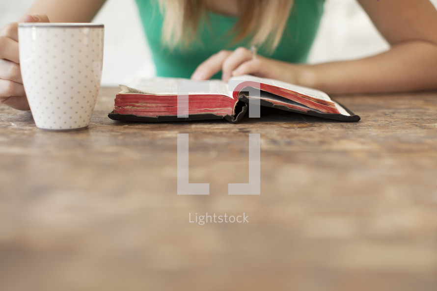 Woman reading the Bible on a wood table with a coffee cup.
