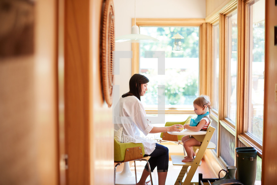 a mother feeding her daughter in a highchair