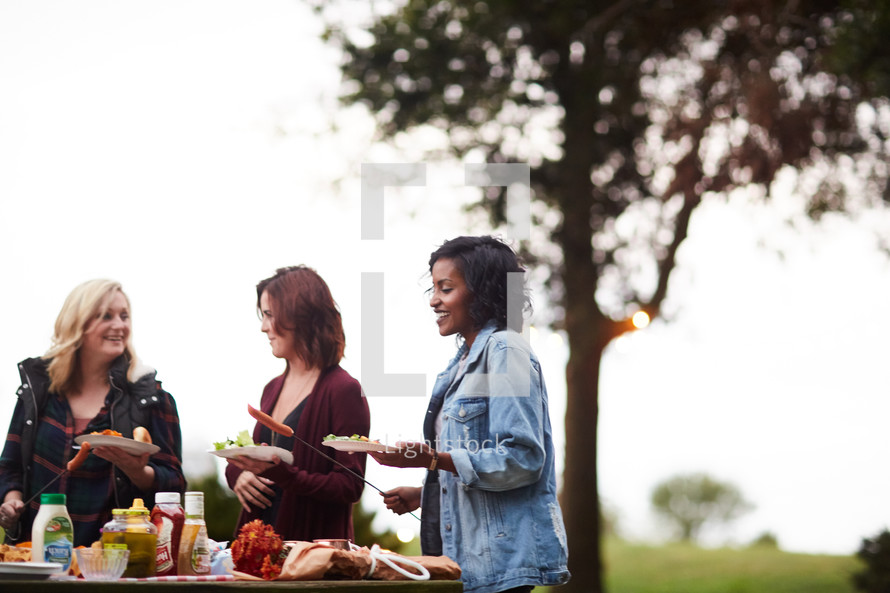 friends gathered around a table outdoors getting food in fall