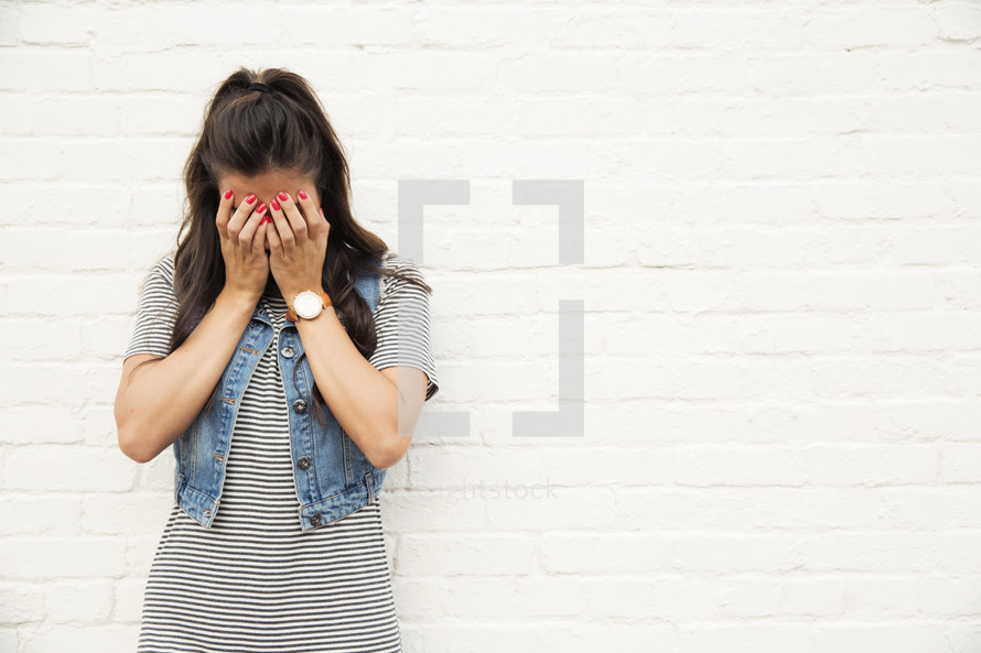 A woman standing in front of a white brick wall with her hands over her face.