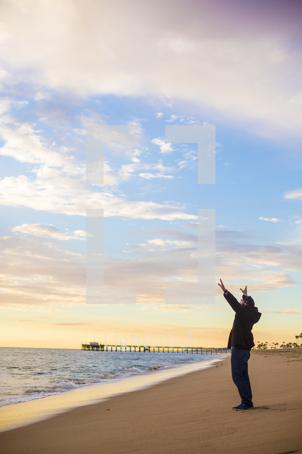 man with raised hands standing on a beach