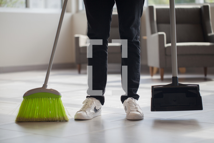 a man with a broom and dust pan
