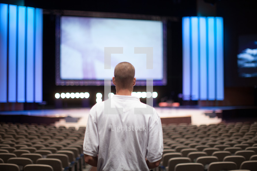 man entering a church and walking down the aisle